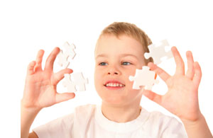 boy focused on holding jigsaw pieces